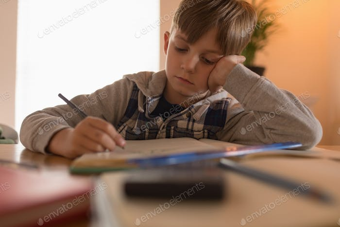 Front view of young Innocent boy concentrating while doing his math homework at home