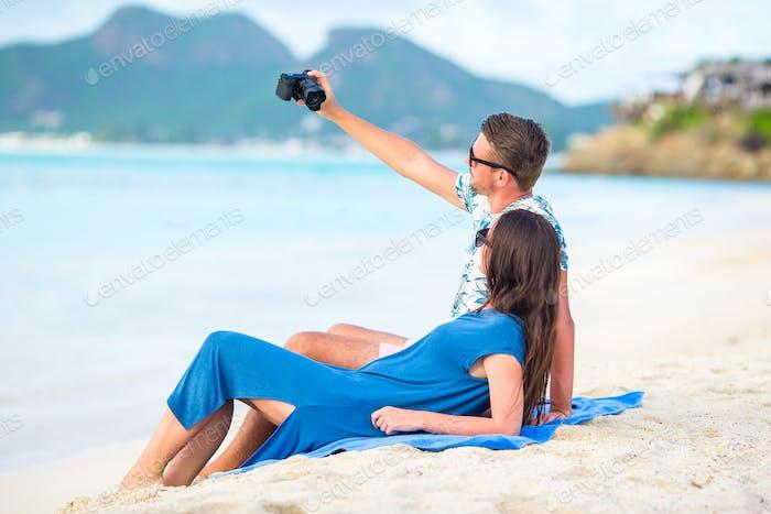 Glückliches Paar, das ein Foto am weißen Strand auf Flitterwochen Urlaub macht
