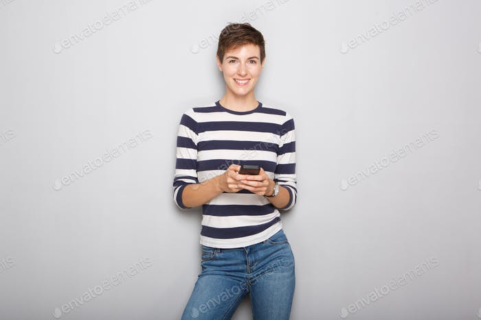 happy young woman holding cellphone against gray background