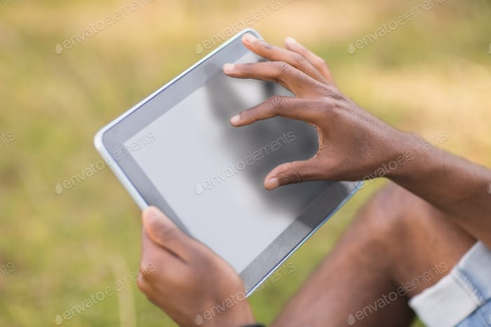 Handsome hipster using his tablet pc on a sunny day