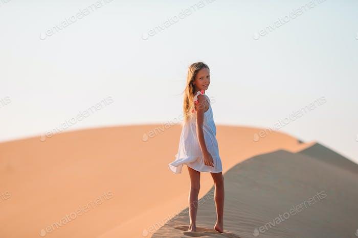 Mädchen unter Dünen in der Wüste in Vereinigte Arabische Emirate