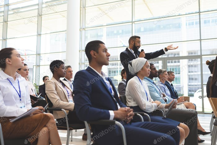 Side view of mixed race businessman asking question during seminar in office building