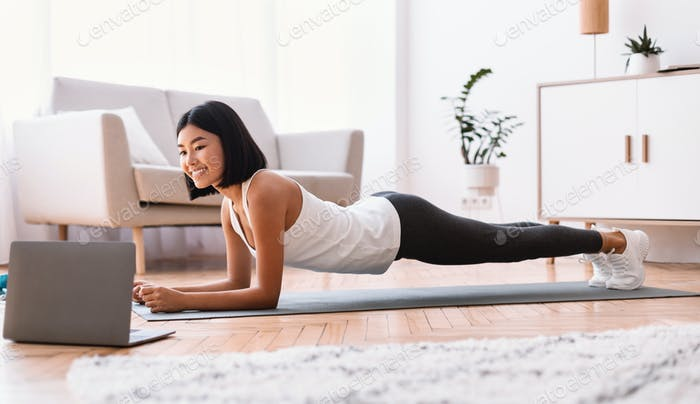 Sporty asian woman doing plank watching tutorial on laptop
