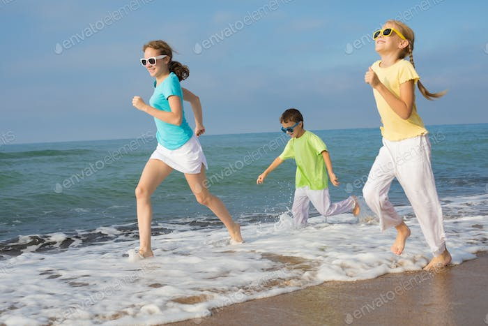 Three happy children running on the beach at the day time.