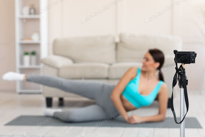 Girl Exercising In Front Of Camera Making Video Workout Indoors