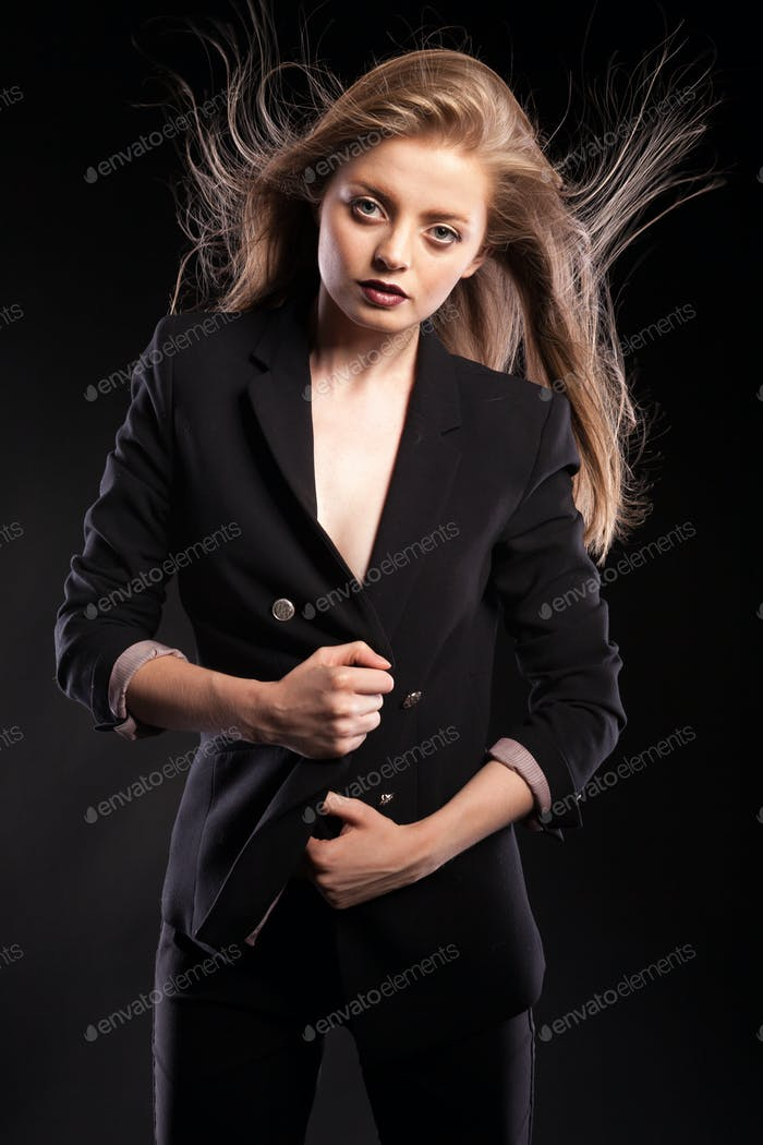Blonde woman posing in fashion style on black background