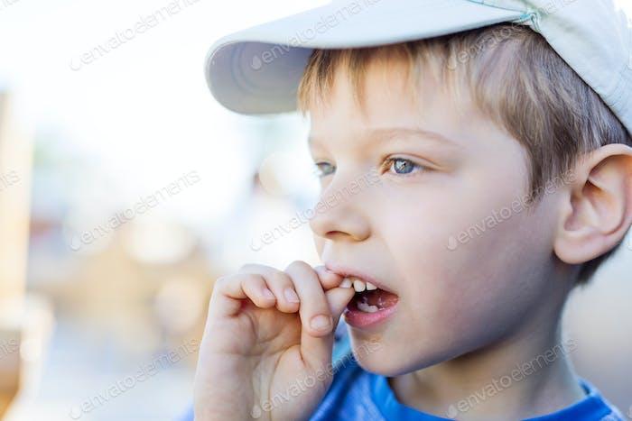 Nahaufnahme des Jungen schüttelt seinen wackeligen Milchzahn mit seinen Finger. Oberer Vorderzahn