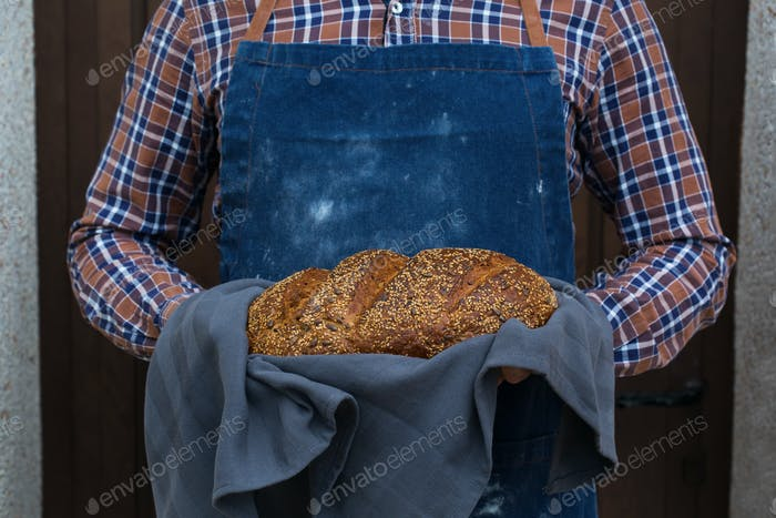 Fresh loaf of homemade rye bread in woman hands
