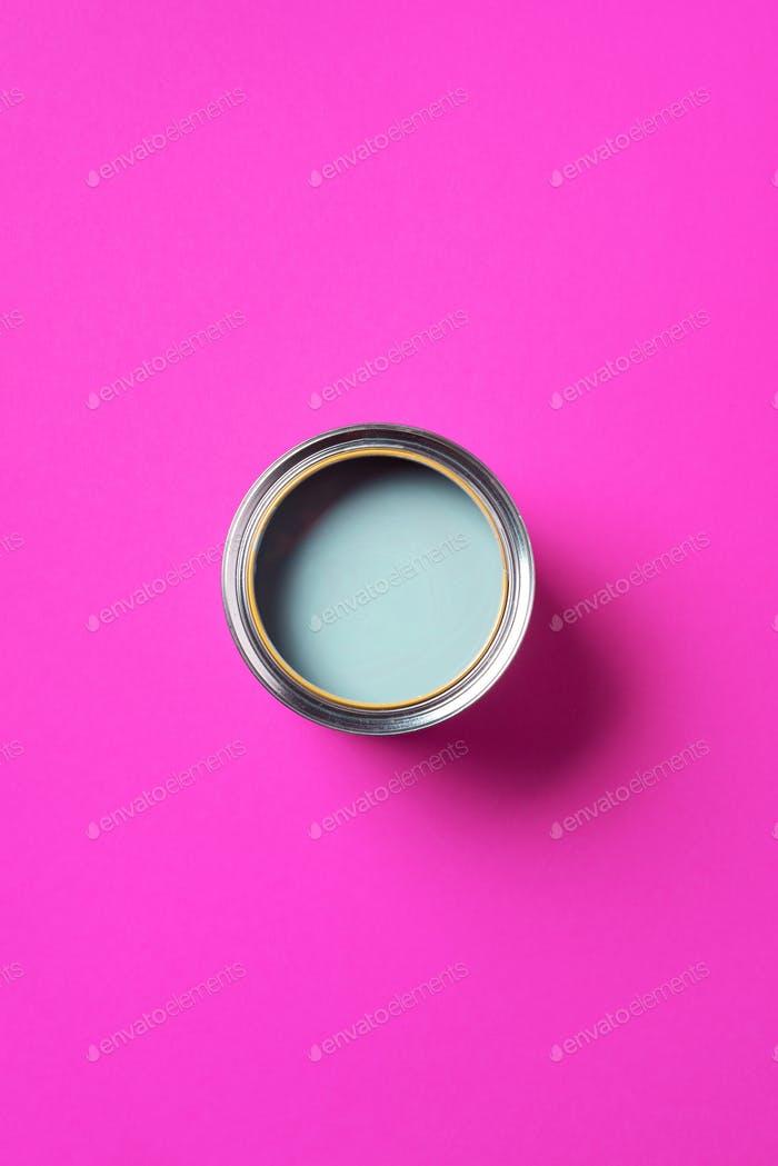 Open paint can with on trendy pink background. Top view, copy space. Appartment renovation, repair