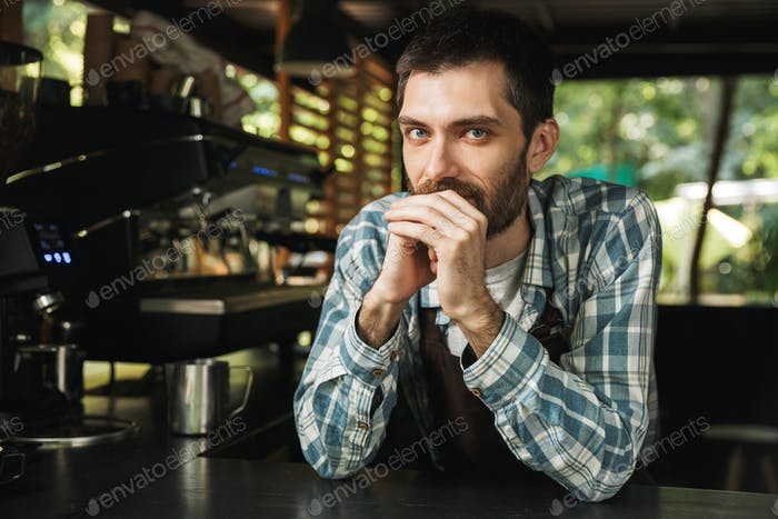 Portrait of bearded barista guy smiling at camera while working