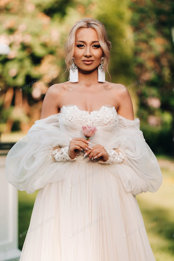 A beautiful bride in a luxurious wedding dress holds a rose and greenery on a green natural