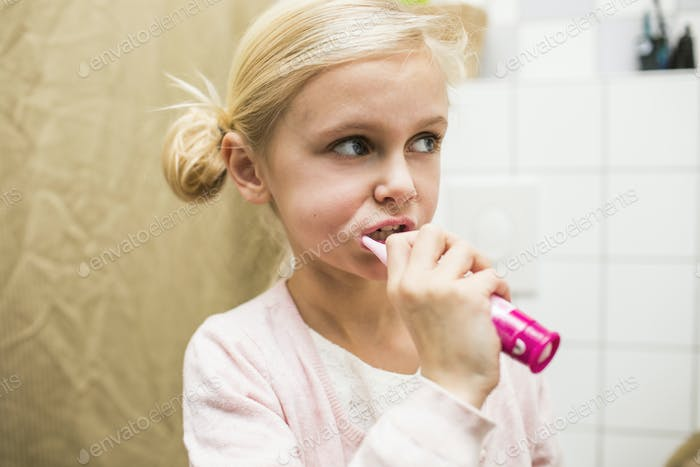 Close-up of girl brushing teeth in bathroom