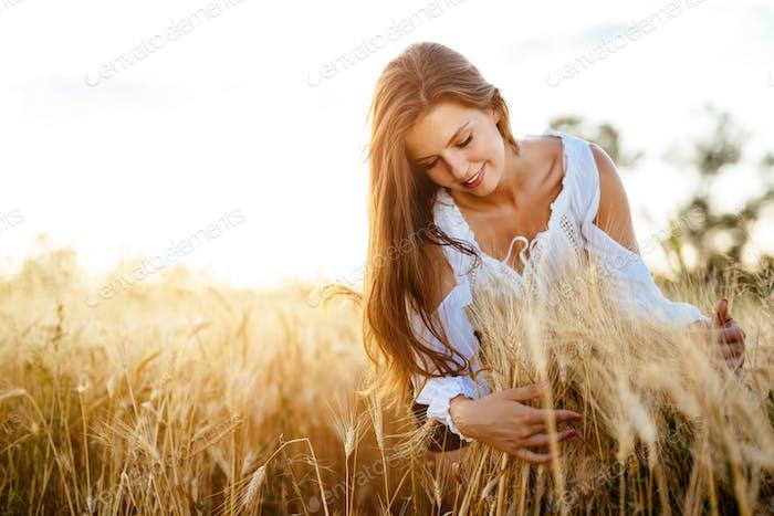 Romantische Frau in Feldern der Gerste