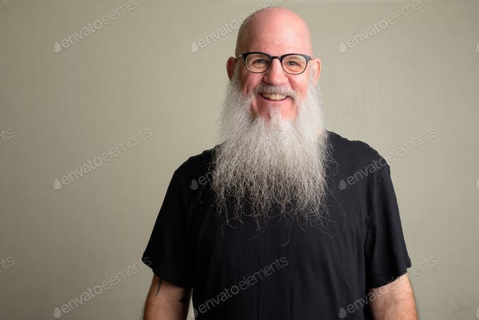Happy mature bald man with long gray beard smiling and wearing eyeglasses