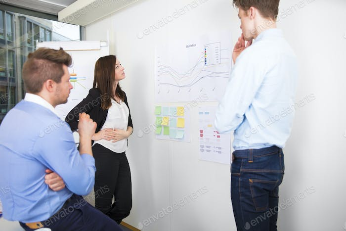 Business Professionals Discussing Over Line Graph In Office