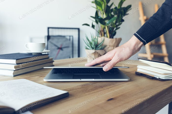 human hand holding laptop at workplace in home office