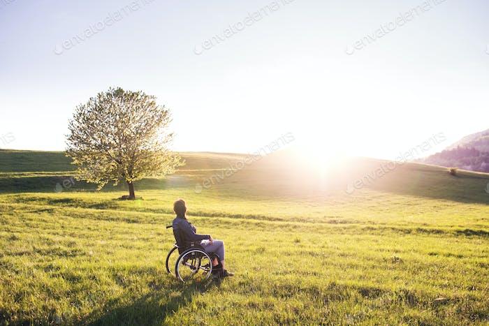 Una Mujer en silla de ruedas en la Naturaleza al atardecer.