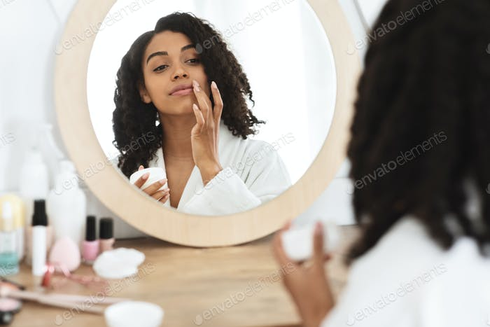 Lips Care. Beautiful Black Woman Applying Moisturising Balsam, Reflecting In Mirror
