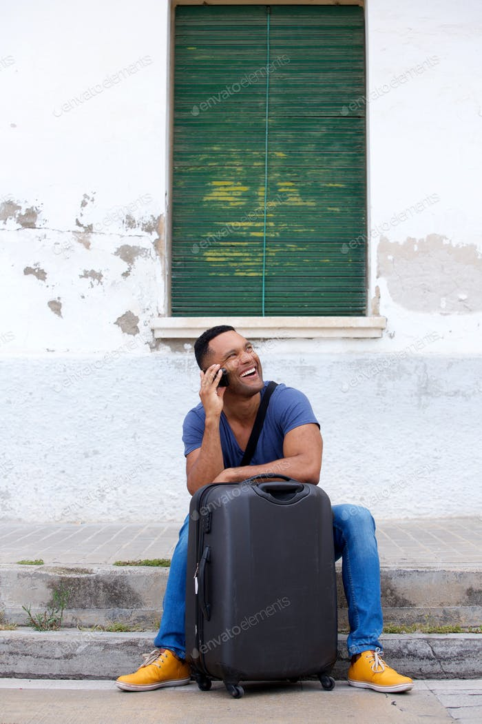 Happy young african man sitting with suitcase and talking on mobile phone