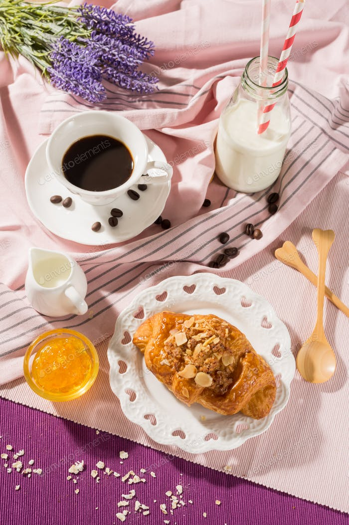 Breakfast set. Bread with jam over the disk on table set background, serve with coffee cup