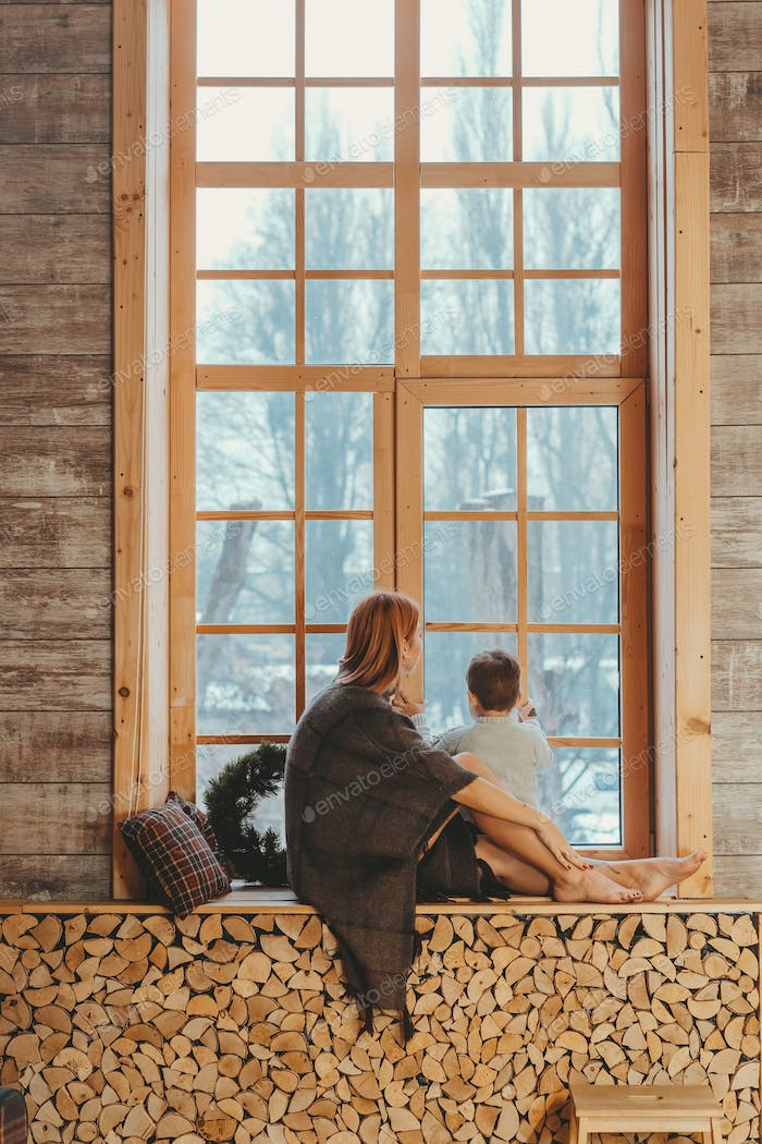 Mom and son sitting on the windowsill and playing