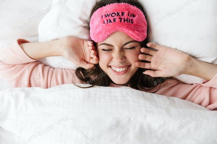 Fröhlich schöne junge Mädchen tragen Pyjamas legen im Bett