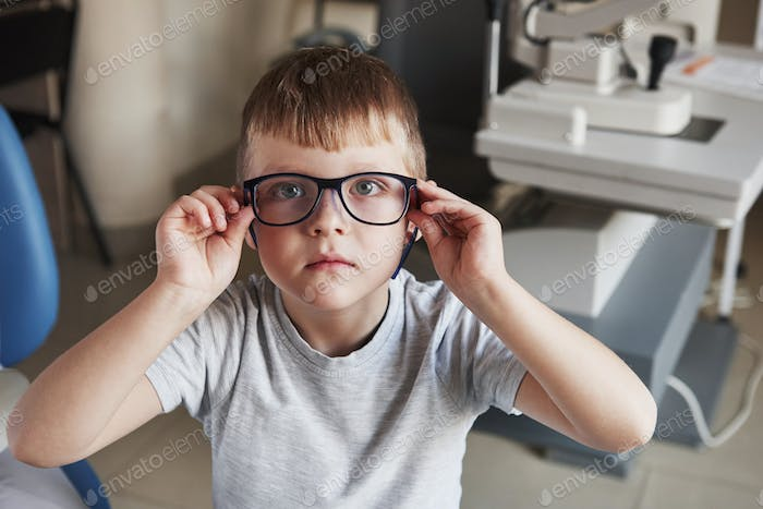 Portrait of kid sitting with glasses in doctor clinic with ophthalmic equipment at background