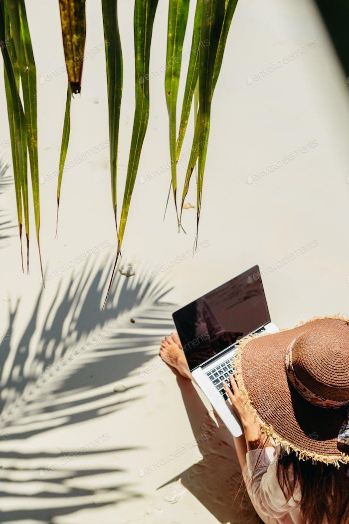 Frau arbeitet aus der Ferne auf Laptop am Strand in Tropen