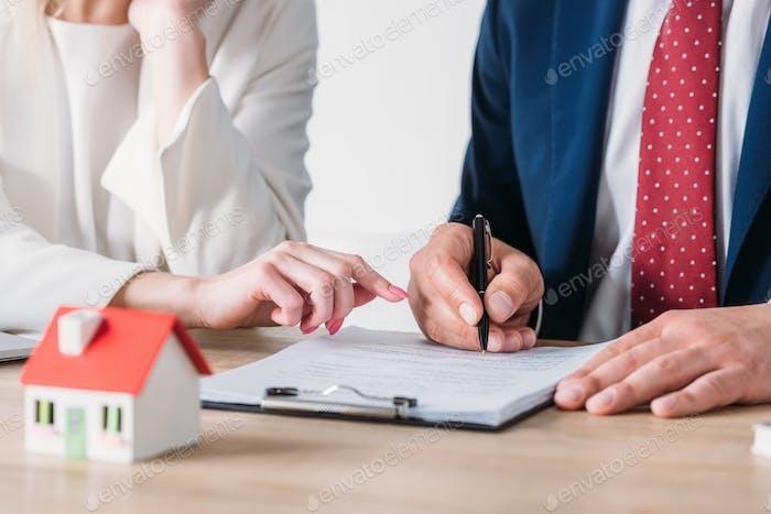 Teilansicht einer Geschäftsfrau, die im Kreditvertrag in der Nähe des Kundenhalters auf den Unterschriftort verweist