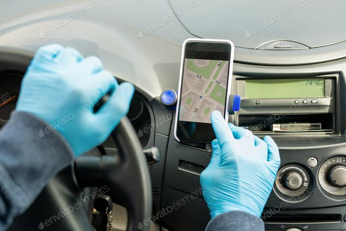 Перчатка руки современного таксиста касания экрана смартфона в автомобиле