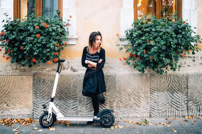 Modern lifestyle details, happy girl with flowers in urban city enjoying the electric scooter.