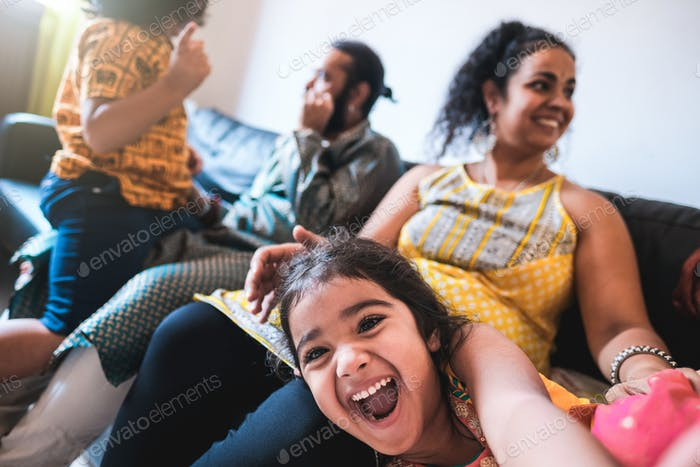 Happy girl child taking selfie with mobile phone camera at home with family in background