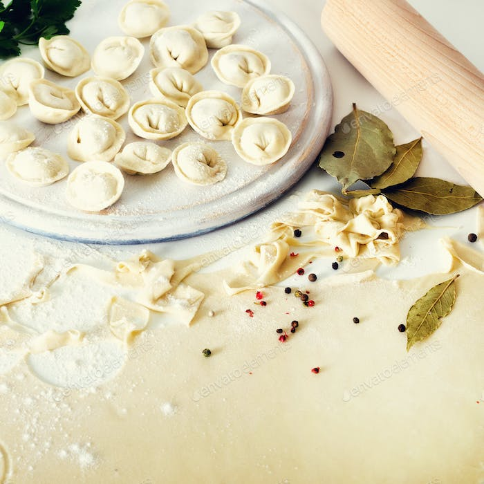 Traditional russian pelmeni, ravioli, dumplings with meat on white concrete background. Parsley