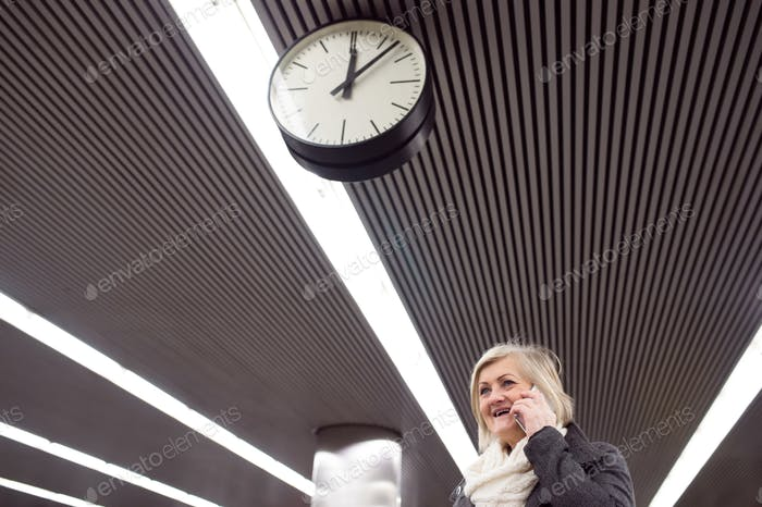 Senior woman at the underground platform, talking on phone