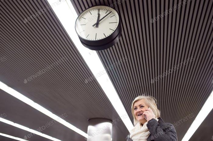 Senior woman at the underground platform, talking on phone
