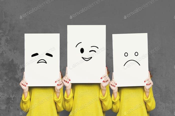 Mädchen bedeckt Gesicht mit weißen Brettern. Set von bemalten Emotionen