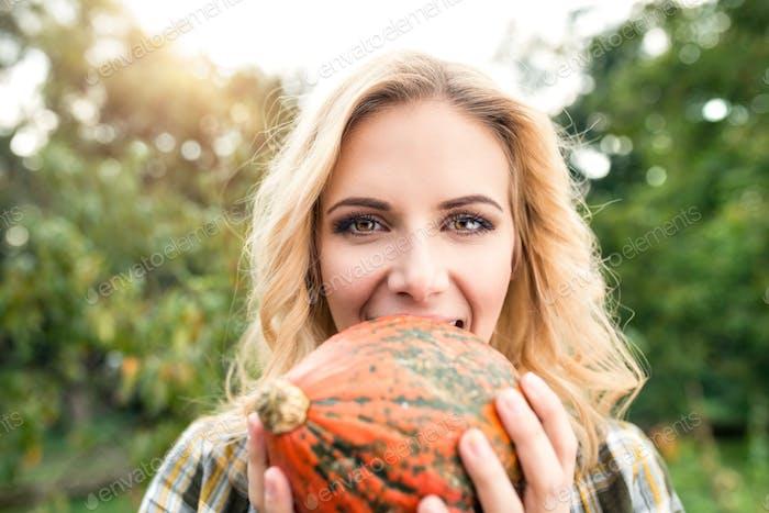 Schöne junge blonde Frau in ihrem Garten Ernte Kürbisse