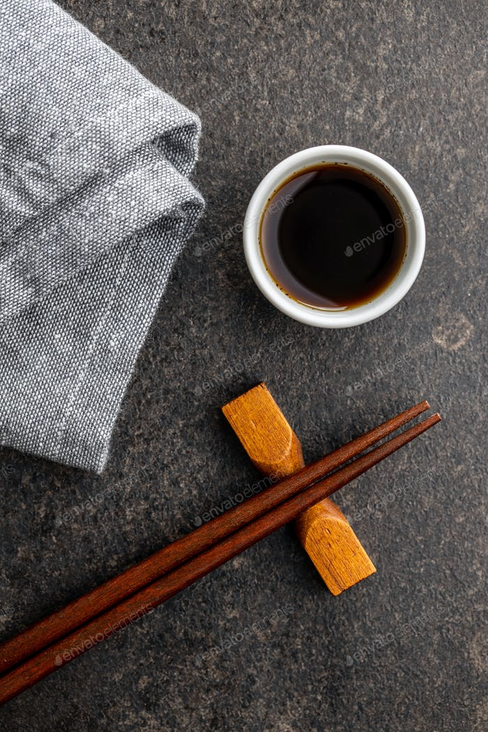 Soy sauce in bowl, chopsticks and napkin.