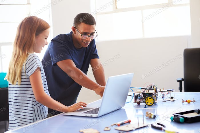 Female Student With Teacher Building Robot Vehicle In After School Computer Coding Class