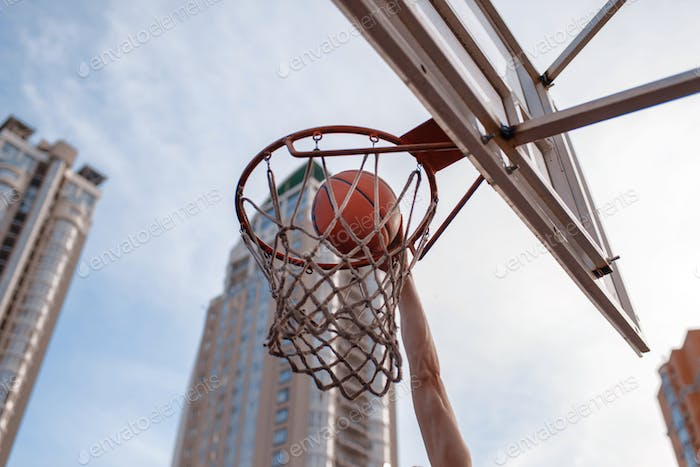 Basketball ball hits the basket outdoor, nobody