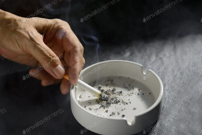 Hand putting the cigarette on an ashtray