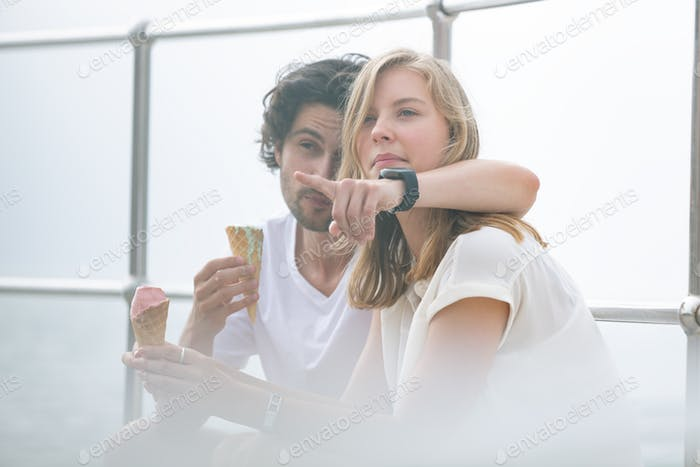 Side view of young Caucasian couple siting at promenade while having ice cream cone on a sunny day