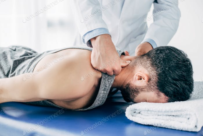 chiropractor massaging neck of man lying on Massage Table with towel