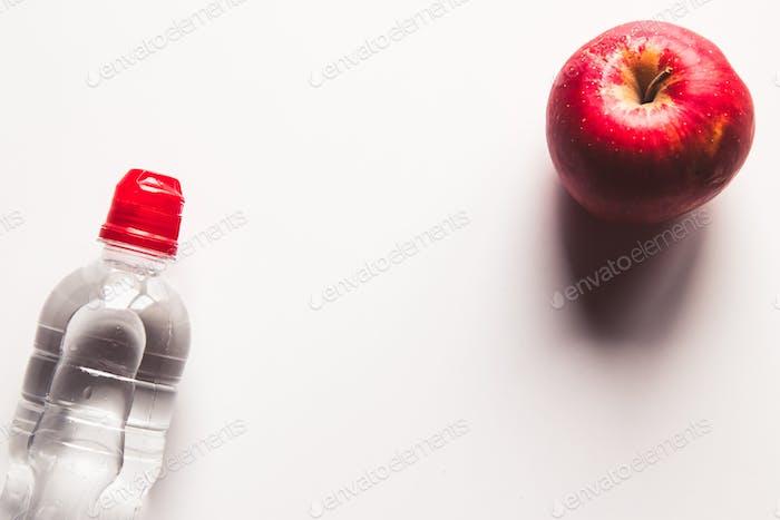 Flasche Mineralwasser und rotem Apfel