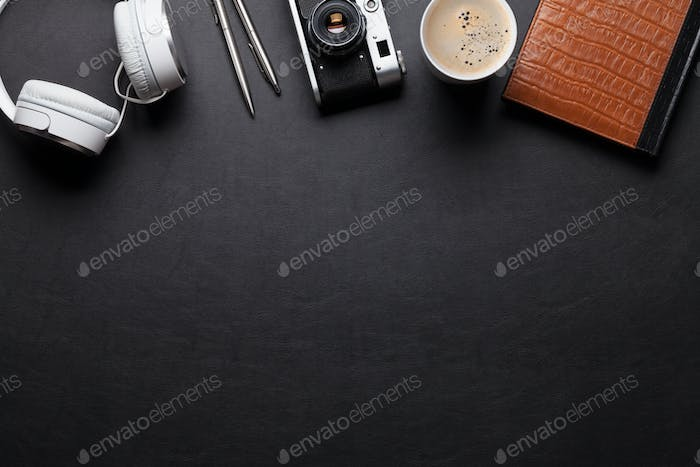 Office desk table with notepad, headphones, camera