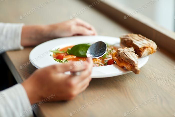 woman eating gazpacho soup at restaurant