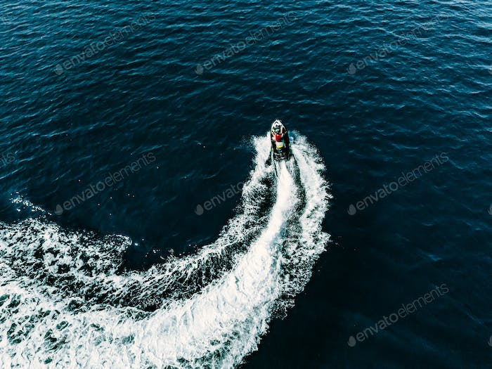 Aerial view of jet skier in blue sea. Jet ski in turquoise clear water racing
