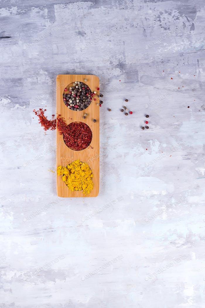 drei Arten von Gewürzen in Holzplatte auf Stein isoliert