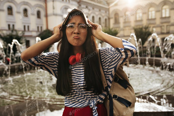 Sad funny woman in eyeglasses, striped shirt and red skirt looks into camera and covers head with m