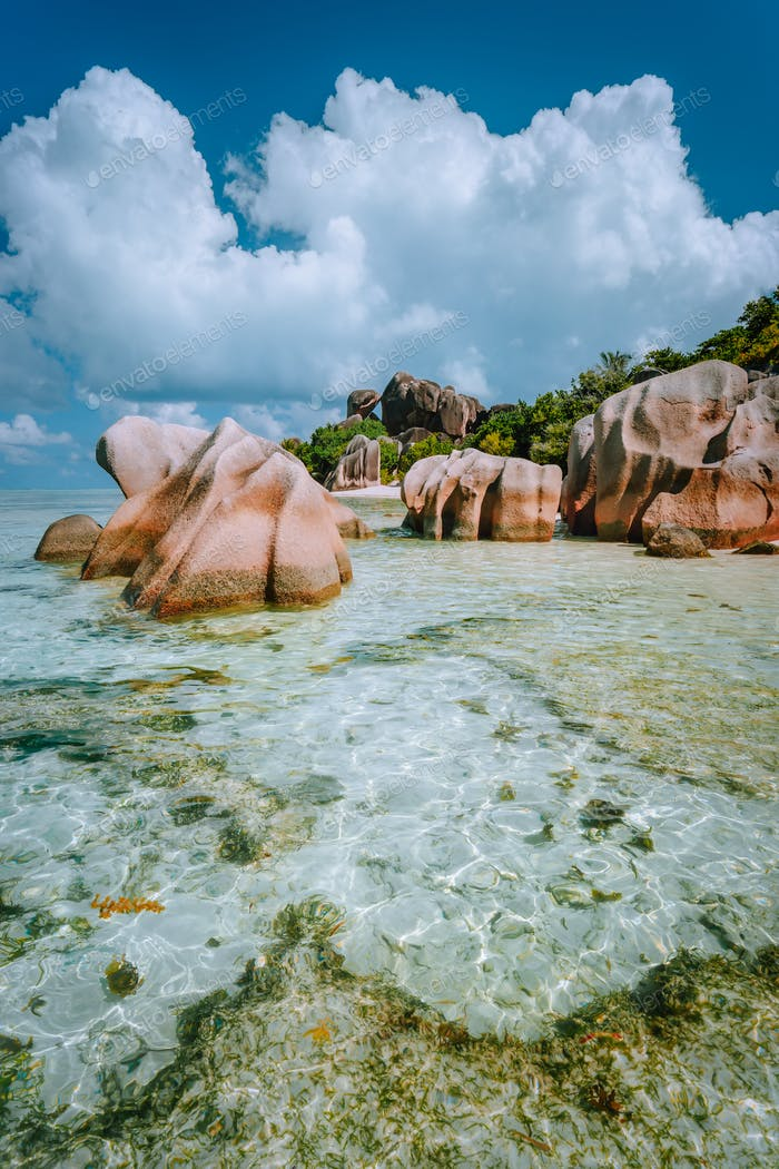 Paradise tropical beach Anse Source d'Argent with shallow blue lagoon, granite boulders and